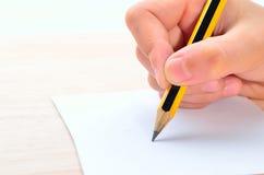 Schreibender Bleistift in der Hand Lizenzfreie Stockbilder