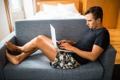 Schreibendes neues Blog geben Seitenansicht des hübschen jungen Mannes bekannt, der seinen Laptop mit Lächeln beim auf der Couch  Stockfotografie
