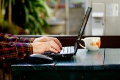 Schreibeninternet der wörter und der Suche eines Mannes auf Notizbuch auf Holztisch an diesem Feiertagsmorgen, Abschluss herauf a Lizenzfreie Stockfotografie