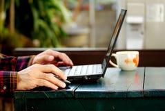 Schreibeninternet der wörter und der Suche eines Mannes auf Notizbuch auf Holztisch an diesem Feiertagsmorgen, Abschluss herauf a stockfotos