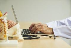 Schreibenlaptop-computer Doktors auf dem Schreibtisch stockbild