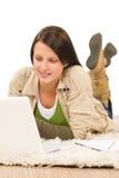 Schreibenliegenfußboden des laptops des Kursteilnehmerjugendlichmädchens Stockfotografie