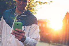 Schreibenmitteilung des glücklichen Mannes an seinem Handy und Gehen auf die Straße Stockfoto
