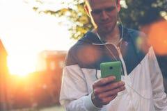 Schreibenmitteilung des jungen Mannes an seinem Handy und Gehen auf die Straße Lizenzfreies Stockbild