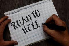 Schreibensanmerkung, die Straße zur Hölle zeigt Geschäftsfoto, das Mann-Handgriff Reise des extrem gefährlichen Durchgangs dunkle stockbild