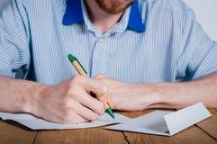 Schreibensbuchstabe des jungen Mannes stockbild