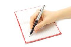 Schreibensfrauenhand im Notizblock Lizenzfreies Stockbild