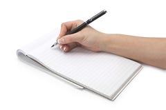 Schreibenshand in einem Notizbuch Stockfotografie