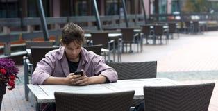 Schreibensmitteilung des jungen Mannes, die bei Tisch sitzt Lizenzfreie Stockbilder