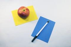 Schreibenspapier und -apfel stockfoto