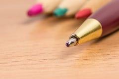 Schreibensstift steht heraus vor dem hintergrund der farbigen Bleistifte lizenzfreie stockbilder