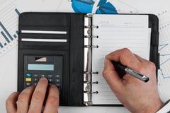 Schreibensstift und Zählung auf einem Taschenrechner stockbild