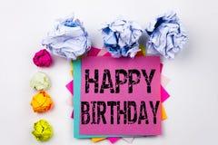 Schreibenstext, der alles Gute zum Geburtstag geschrieben auf klebrige Anmerkung im Büro mit Schraubenpapierbällen zeigt Geschäft Stockfotografie