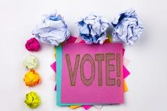 Schreibenstext, der die Abstimmung geschrieben auf klebrige Anmerkung im Büro mit Schraubenpapierbällen zeigt Geschäftskonzept fü Stockfoto