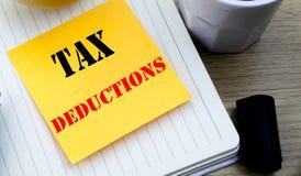 Schreibenstext, der Steuerabzüge zeigt Geschäftskonzept für geschriebenes leeres Papier der klebrigen Anmerkung des Finanzankomme Lizenzfreie Stockfotografie