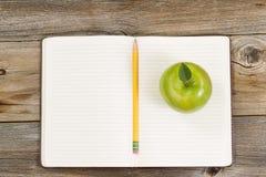 Schreibenswerkzeuge und -Snack für Schule oder Büro auf rustikalem hölzernem BO Lizenzfreie Stockfotografie