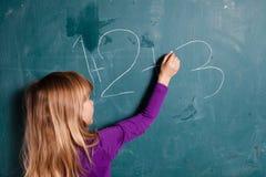 Schreibenszahlen des jungen Mädchens auf Tafel Lizenzfreies Stockfoto