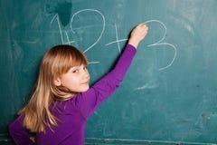 Schreibenszahlen des jungen Mädchens auf Tafel Lizenzfreies Stockbild
