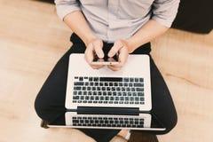 Schreibentextnachricht des Draufsichtmannes an seinem intelligenten Telefon während sittin Lizenzfreie Stockfotos