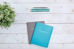Schreibheft, Bleistifte und Stift auf einer weißen Tabelle mit einer Blume in einem Topf Lizenzfreie Stockfotografie