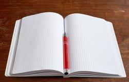 Schreibheft und roter Stift Lizenzfreie Stockfotografie
