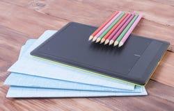 Schreibhefte, Bleistifte und die Tablette auf einer Holzoberfläche Stockfoto