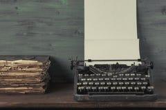 Schreibmaschine mit den Papier- und alten Büchern Lizenzfreie Stockfotos