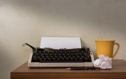 Schreibmaschine mit Kaffeetasse und Stift Lizenzfreies Stockfoto