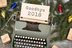 Schreibmaschine mit Text 'Auf Wiedersehen 2018 ', Fichtenzweigen und Geschenkboxen auf einem Holztisch lizenzfreie stockfotos