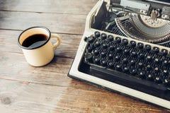 Schreibmaschine und ein Becher heißer Kaffee auf einem Holztisch Stockfotografie
