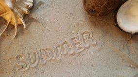 Schreibt den Wortsommer, auf den Sand des Strandes mit einer Muschel und einer Kokosnuss stockfotografie