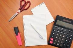 Schreibt in ein Notizbuch herum Berechnungen auf einem Taschenrechner lizenzfreie stockfotos