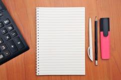 Schreibt in ein Notizbuch herum Berechnungen auf einem Taschenrechner stockfotografie