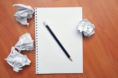 Schreibt in ein Notizbuch um ein zerknittertes Papier lizenzfreie stockfotografie