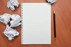 Schreibt in ein Notizbuch um ein zerknittertes Papier lizenzfreie stockbilder