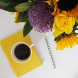 Schreibtisch-Bild mit Kaffee und Blumen Stockfoto