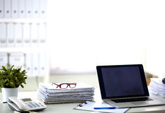 Schreibtisch, den ein Stapel Computerpapierberichte bearbeiten lizenzfreie stockbilder