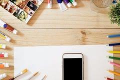Schreibtisch des Künstlers und Smartphone auf Schreibtisch Lizenzfreie Stockbilder