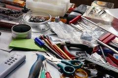 Schreibtisch durcheinandergeworfen mit Werkzeugen Stockfotografie