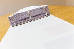 Schreibtisch in einem Büro mit dem Ordner voll vom Papierhintergrund Lizenzfreie Stockbilder