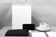 Schreibtisch: Kaffee mit Telefon, Kalender, Notizblock Schwarzweiss Stockfotos