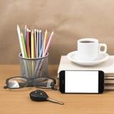 Schreibtisch: Kaffee und Telefon mit Autoschlüssel, Brillen, Stapel von Stockfotos