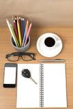 Schreibtisch: Kaffee und Telefon mit Schlüssel, Brillen, Notizblock, penci Stockfotografie