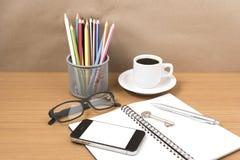 Schreibtisch: Kaffee und Telefon mit Schlüssel, Brillen, Notizblock, penci Lizenzfreie Stockfotografie