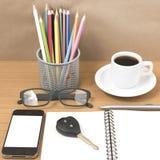 Schreibtisch: Kaffee und Telefon mit Schlüssel, Brillen, Notizblock, penci Lizenzfreie Stockfotos