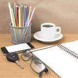Schreibtisch: Kaffee und Telefon mit Schlüssel, Brillen, Notizblock, penci Stockfotos