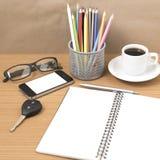 Schreibtisch: Kaffee und Telefon mit Schlüssel, Brillen, Notizblock, penci Lizenzfreies Stockbild