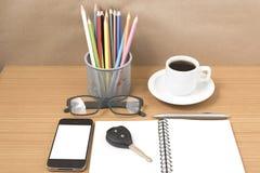 Schreibtisch: Kaffee und Telefon mit Schlüssel, Brillen, Notizblock, penci Stockbilder