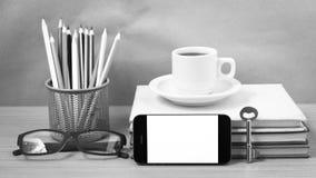 Schreibtisch: Kaffee und Telefon mit Schlüssel, Brillen, Stapel des Buches Stockfotografie