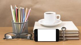 Schreibtisch: Kaffee und Telefon mit Schlüssel, Brillen, Stapel des Buches Lizenzfreie Stockfotografie